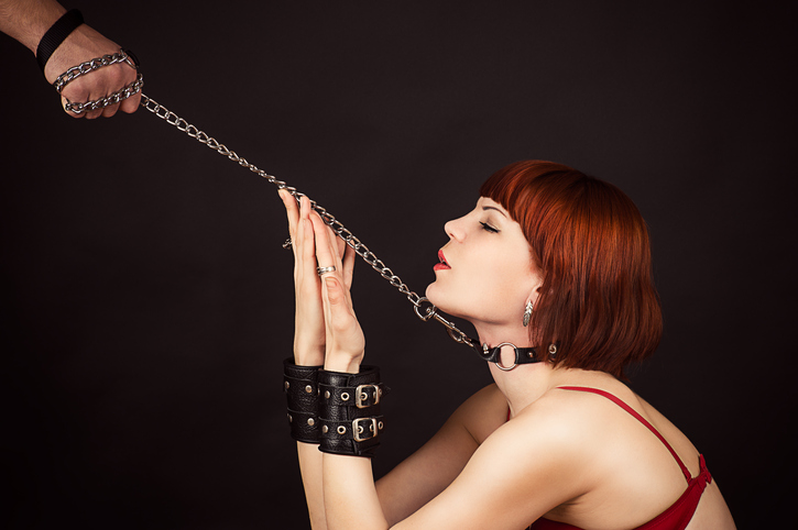 Woman being led by a bondage collar